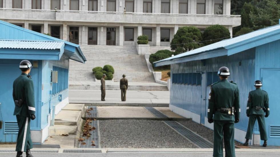 <strong>PÅ VAKT:</strong> Betongkanten midt mellom byggene markerer grensa mellom sør og nord.  23. november 1984, oppsår en voldsom skuddveksling mellom partene da den sovjetiske gjesten Vasily Matusak plutselig tar beina fatt og sprinter over murkanten til Sør-Korea. I den 40 minutter lange skuddvekslingen som følger, drepes tre nordkoreanere og fem blir såret. Mens bare en sørkoreaner drepes, og en såres. Foto: Kristoffer Egeberg
