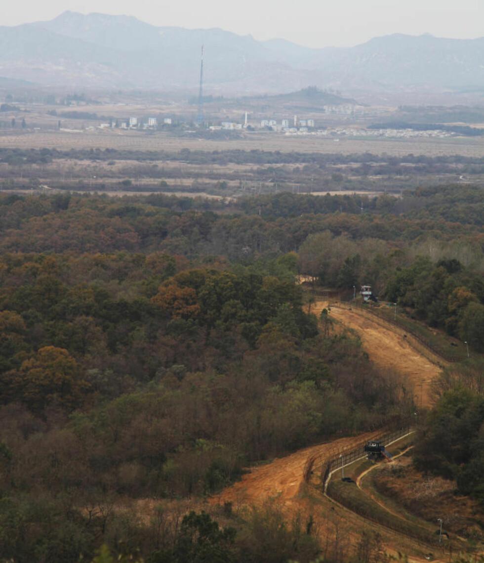 <strong>«DEMILITARISERT»:</strong> Grensa mellom Nord- og Sør-Korea er den best bevoktede i verden. Trukket langs den 38. breddegrad, 250 kilometer lang, og omlag fire kilometer bred. I bakgrunnen ser du en nordkoreansk propagandaby. Byggene er tomme skall. «Innbyggerne» blir busset inn om dagen for å skape aktivitet i gatene slik at den ser attraktiv og levende ut for sørkoreanske beskuere. Flaggstangen var med sine 160 meter verdens høyeste, frem til Aserbajdsjan og Tadsjikistan bygget høyere.  Foto: Kristoffer Egeberg