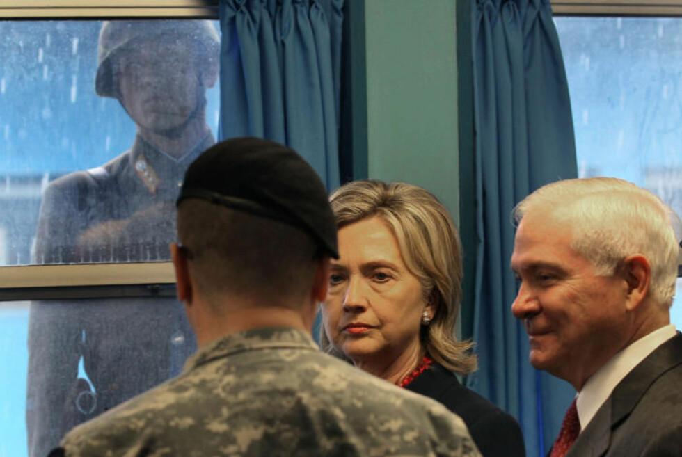 <strong>ÅRETS BILDE:</strong> Nyhetsbyrået AFP plukket ut dette som ett av årets bilder i 2010 da Hillary Clinton og Robert Gates gjestet fellessonen og konferanserommet mens en nordkoreansk soldat følger nøye med.   Foto: AFP/MARK WILSON/NTB-SCANPIX