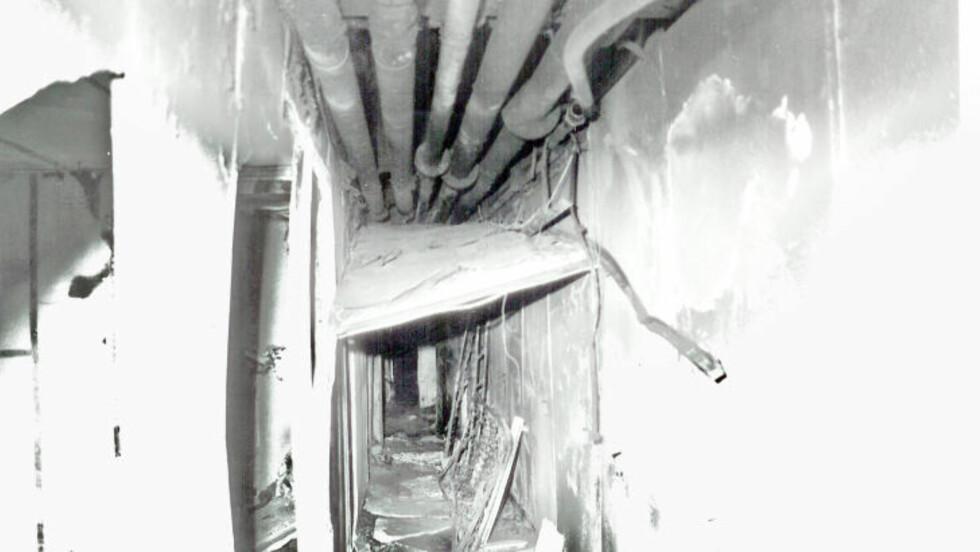 ARNESTED: Etter den voldsomme hydraulikkoljebrannen så det slik ut i lugarseksjonen. Himlingsplatene hadde falt ned, veggplater var smadret - og hydraulikkoljerøret i taket var bøyd horisontalt ut av en kopling. Ekspertpanelet avviser muligheten for at dette har skjedd som følge av brannen. Foto: Politiet