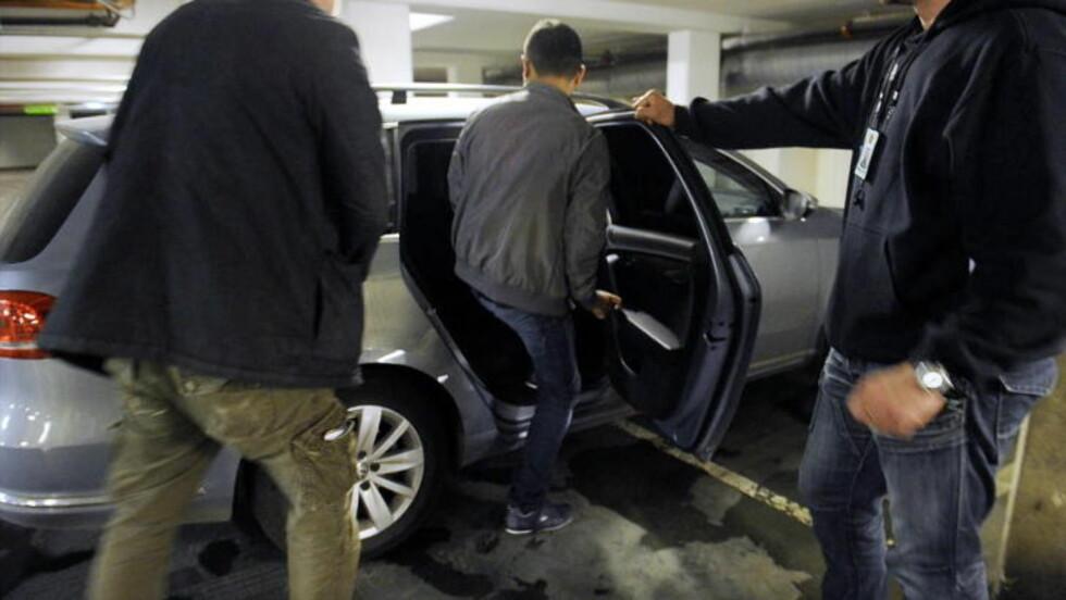 PÅGREPET: Her blir en av eierne av et bilvaskeri på Grønland pågrepet av politiet. Politiet har siktet 25-åringen for å ha utnyttet sårbare mennesker til å ha jobbet 12-timersdager for 33 kroner i timen. Selv nekter han for forholdene, og mener han betalte ca. 130 kroner i timen. Foto: JOHN TERJE PEDERSEN/DAGBLADET