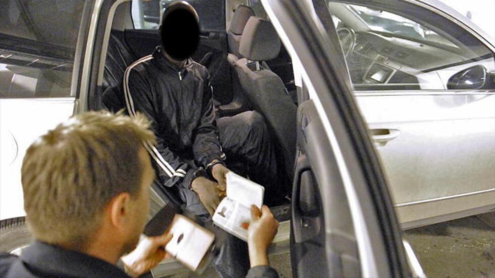 SJEKKER ID:En politimann undersøker ID-en til en afrikansk mann, som politiet mistenker har falsk ID.  Foto: JOHN TERJE PEDERSEN/DAGBLADET