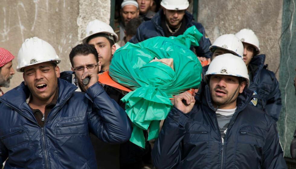 I DYP SORG: For ett år siden ble en av de frivillige i De hvite hjelmene, Ilias Mahmoud al-Taweel, drept mens han var ute for å redde ut mennesker etter et bombeangrep. Her blir han båret av sine kamerater, på vei for å gravlegges. Foto: Feras Domy / Ap / Scanpix