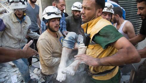 FRIVILLIGE PÅ JOBB: De får ikke betalt, men De hvite hjelmene er alltid de første som er på plass etter bombeangrep i opprørskontrollerte deler av Syria. Her tas en person ut av en ødelagt bygning i Aleppo i sommer. Foto: Karam al-Masri / Afp / Scanpix