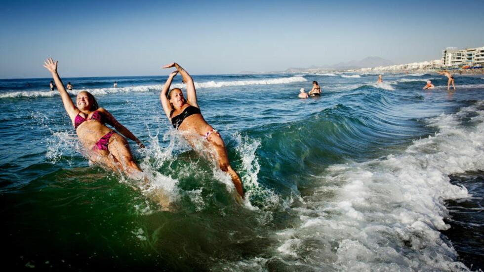FERIEDRØM: Mange planlegger ferie til varmere strøk nå om vinteren. Her kaster Kristine Stetzer og Julie Henriksen fra Tønsberg seg ut i havet fra Rethymnon-stranda. Foto: JOHN T. PEDERSEN