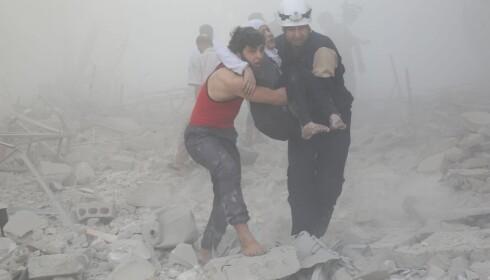 NOK EN BOMBE: En kvinne blir båret i sikkerhet etter at en bombe slo ned i nabolaget hennes. Foto: Khaled Khatib