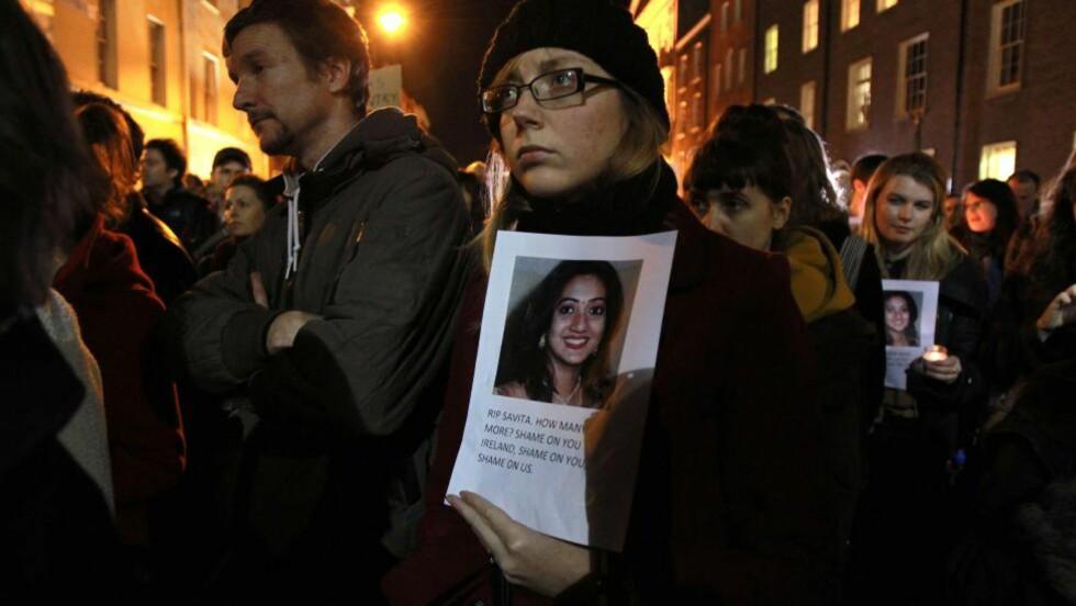 PROTESTERER: Folk i Irland holder bilde av Savita Halappanavar mens de protesterer utenfor parlamentet i Irland. De krever å få legalisert abort AFP / PETER MUHLY