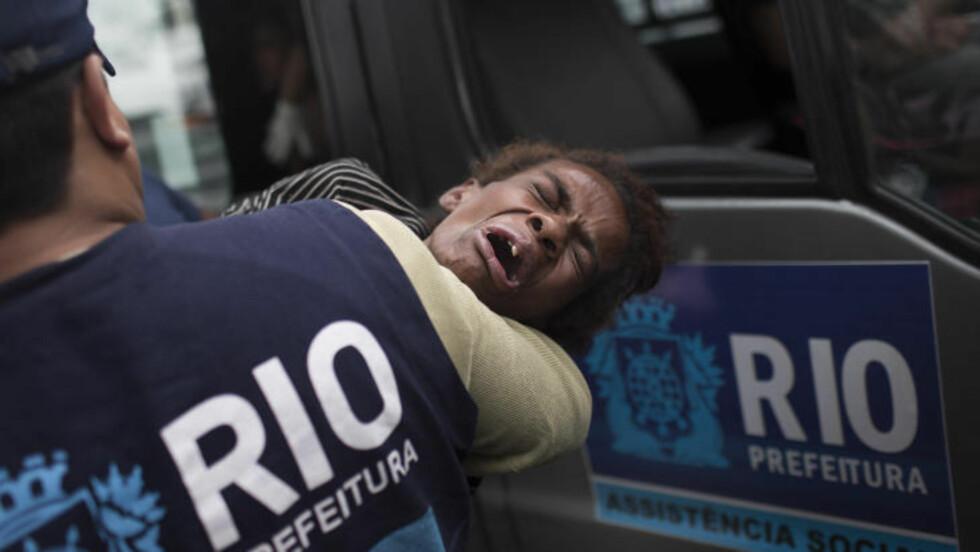 GRÅTER En gråtende dame blir båret til en ventende bil som skal frakte henne til et hulsy der hun vil få behandling av sosialarbeidere. Foto: AP / Felipe Dana