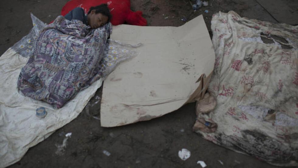 SOVER: En kvinne sover uforstyrret midt i alt oppstyret.Foto: AP / Felipe Dana