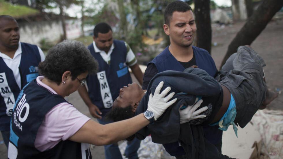 """STOR-AKSJON: Rusmisbrukere blir fraktet ut av """"Crackland"""" under en stor politiaksjon i går. Her blir en gutt båret av sosialarbeidere til et felles hulsy. Foto: AP / Felipe Dana"""