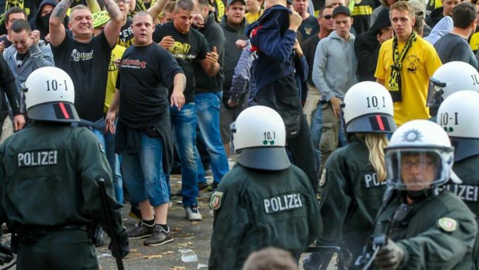 AGGRESSIVT: Det er scener som dette det tyske fotballforbundet vil til livs. Her forsøker politiet å holde supportere fra Borussia Dortmund og Schalke 04 fra hverandre i forbindelse med kampen 20. oktober. Foto: NTB Scanpix