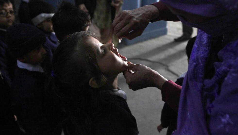 DRÅPER: En kvinne gir her vaksinedråper til et barn i Lahore. Foto: REUTERS/Mohsin Raza/NTBScanpix