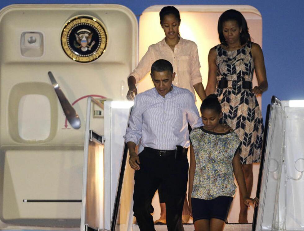 AVBRYTER FERIEN: Kona Michelle og døtrene Malia og Sasha blir igjen på Hawaii når Obama reiser tilbake til Washington DC i kveld. Her går de av flyet ved Pearl Harbor-basen i Honolulu 22. desember. 2012. Foto: Gerald Herbert / AP Photo / NTB Scanpix