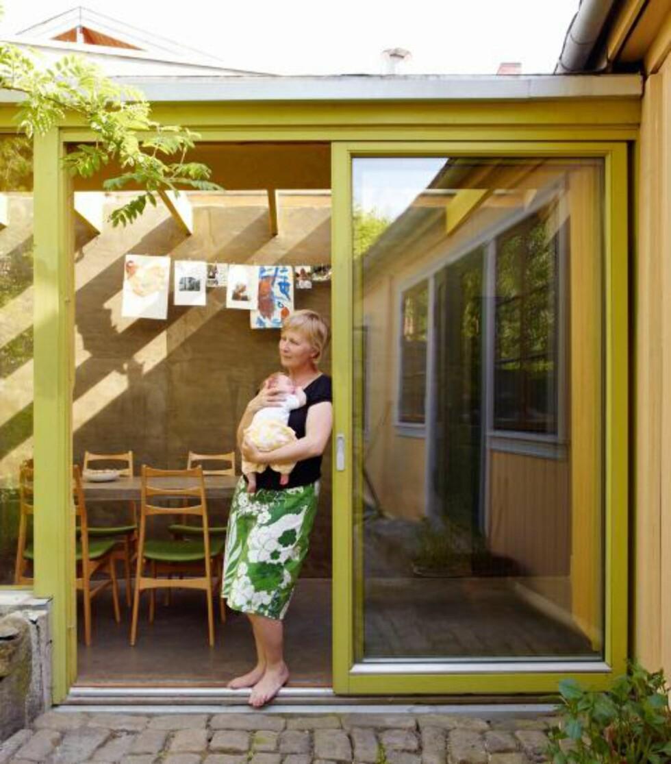 SENTRALT PLASSERT: Fra terskelen til den brostensbelagte uteplassen har Ane Senstad Guldahl kontakt både med kjøkkenet i tilbygget og med det gamle huset. Det er her trafikken er størst. Foto: Ragnar Hartvig