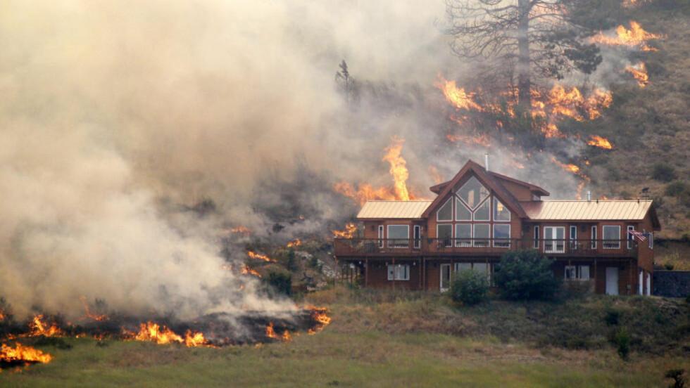 OMRINGET AV FLAMMER: Huset i Washington ble omringet av skogbrann tidligere denne uken. Foto: Elaine Thompson / AP / NTB scanpix.