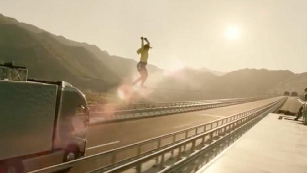 LIVSFARLIG: Faith Dickey forsøker å balansere over linen, samtidig som to trailere kjører i full fart mot en tunnel.
