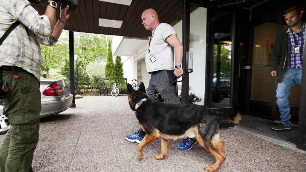 POLITIHUND: I 12.30-tida gikk flere etterforskere og en hundefører inn i bygningen som rommer boligen til mannen som er siktet for falsk forklaring. Bare en snau halvtime seinere var politiet ferdige med akkurat denne undersøkelsen. Foto: HENNING LILLEGÅRD