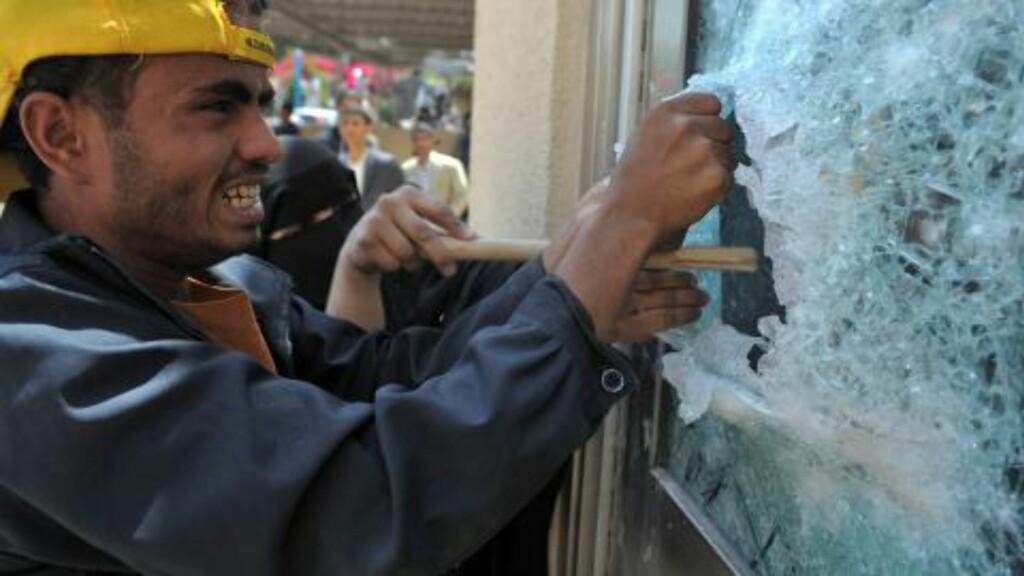 KNUSER VINDUER: Demonstrantene prøver å ta seg inn i ambassaden på alle mulige måter. Foto: EPA