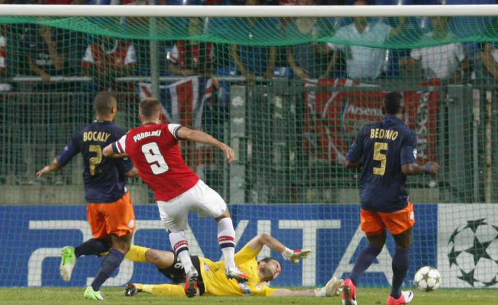 Arsenal's Lukas Podolski shoots and scores the first goal for his team during  their Champions League soccer match against Montpellier at the Stade de la Mosson stadium in Montpellier, September 18, 2012.     REUTERS/Philippe Laurenson (FRANCE  - Tags: SPORT SOCCER TPX IMAGES OF THE DAY)