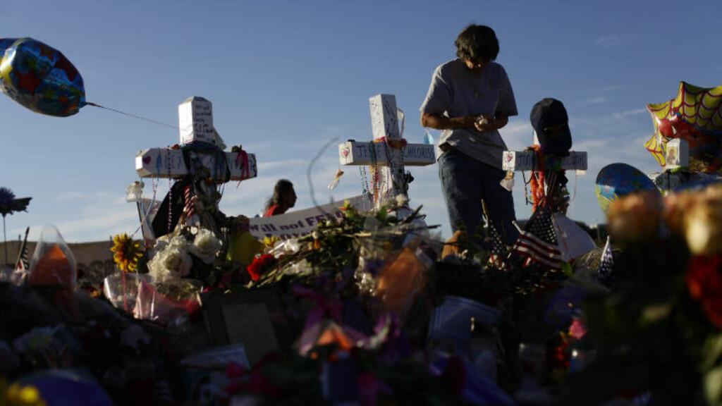 KINOMASSAKRE: En kvinne minnes ofrene ved et minneskmerke som er bygget rett over gata fra der skyteepisoden fant sted. Foto: Joshua Lott/ Getty Images/AFP