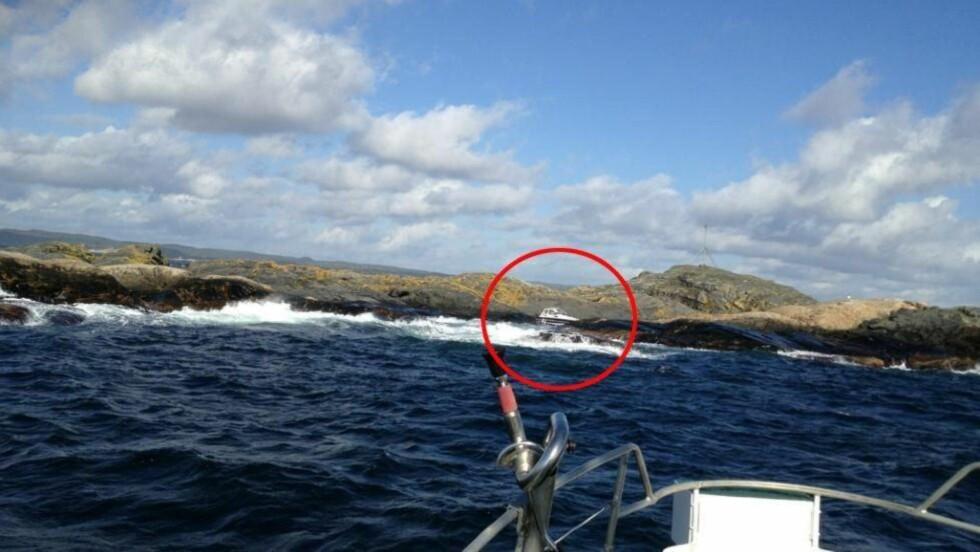 STÅR BOM FAST:  Fritidsbåten på 26 fot står bom fast innenfor Ytre Stråholmstein på Bamblekysten. Foto: Redningsselskapet.