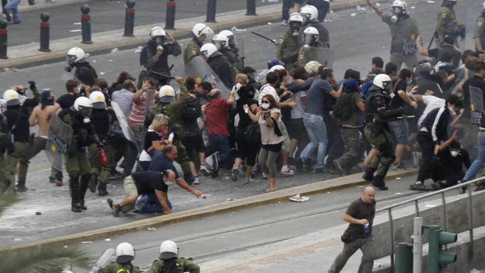 RASENDE DEMONSTRANTER: Rundt 30 000 grekere ga blaffen i demonstrasjonsforbudet og samlet seg på Syntagma-plassen for å marsjere mot nasjonalforsamlingen for å vise sin misnøye med Merkels besøk. Foto: Grigoris Siamidis / REUTERS / NTB SCANPIX