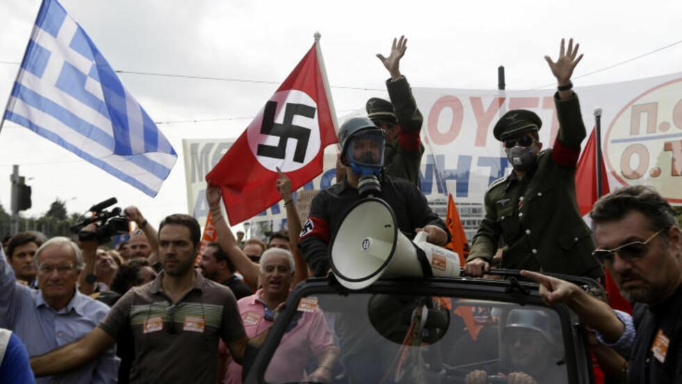 FRUSTRERTE GREKERE: Demonstranter utkledd som nazister i Hellas da Merkel besøke det kriserammede landet tidligere denne uken. Foto: Lefteris Pitarakis / AP Photo