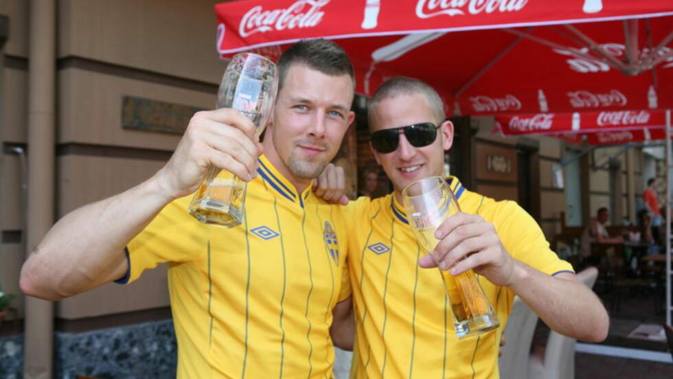 GLEDER SEG: Christian Gustavsson (t.v) og Johan Olausson er stinne av optimisme før Sveriges åpningskamp mot Ukraina i kveld. De lader allerede opp med en øl. Foto: Tore Ulrik Bratland