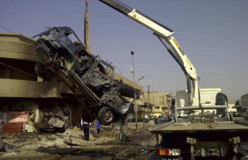 BOMBEANGREP: En utbrent bil fjernes fra plassen der hvor flere titalls personer ble drept i et bomeangrep onsdag. Angrepet var rettet mot sjiamuslimske pilgrimer, og skjedde flere steder i Iraks hovedstad Bagdad. Foto: SAAD SHALASH / REUTERS / NTB SCANPIX