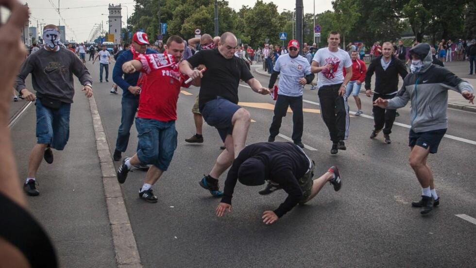 POLAKKER STO BAK: Polakker begynte slåsskampen da russere og polakker barket sammen før Polen møtte Russland i EM i Warszawa tirsdag. AFP PHOTO/WOJTEK RADWANSKI