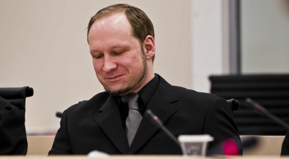 SMILER: Anders Behring Breivik har smilt mye under framleggingen av den første rettspsykiatriske rapporten i dag. Breivik er som kjent svært uenig i psykiaterne Synne Sørheim og Torgeir Husbys konklusjon om at han var strafferettslig utilregnelig 22. juli.  Foto: Vegard Grøtt / NTB scanpix