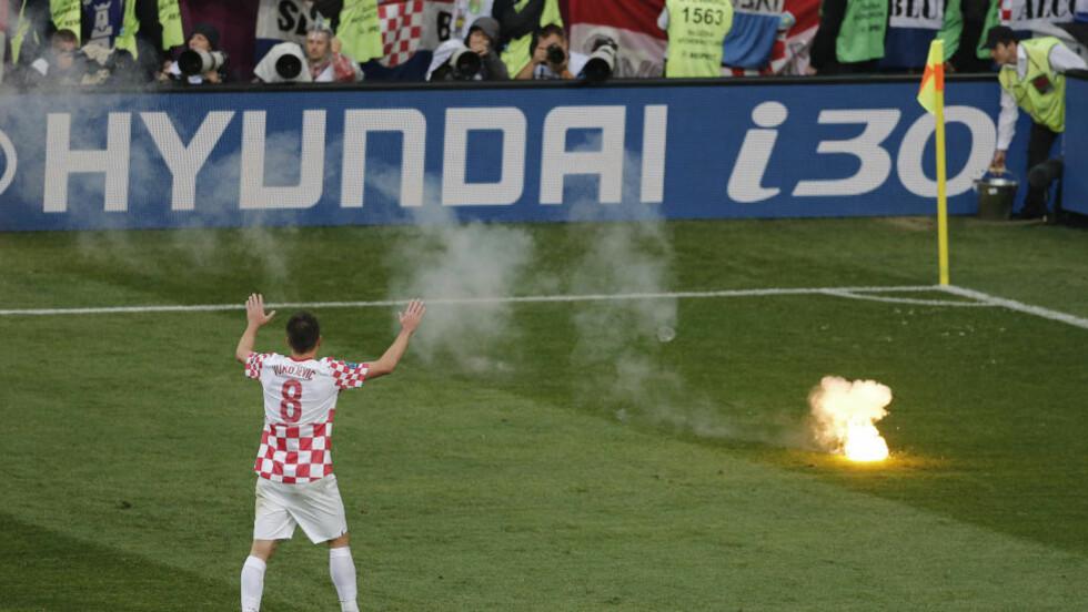 FYRVERKERI: Ognjen Vukojevic forsøker å roe fansen som kaster fyrverkeri på banen. Foto: AP Photo/Anja Niedringhaus