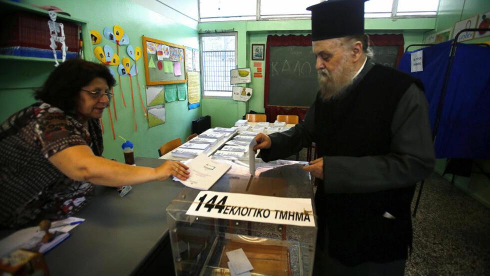 VIKTIG VALG: En prest har møtt opp for å gi sin stemme i Aten søndag morgen. Foto: REUTERS/Yannis Behrakis