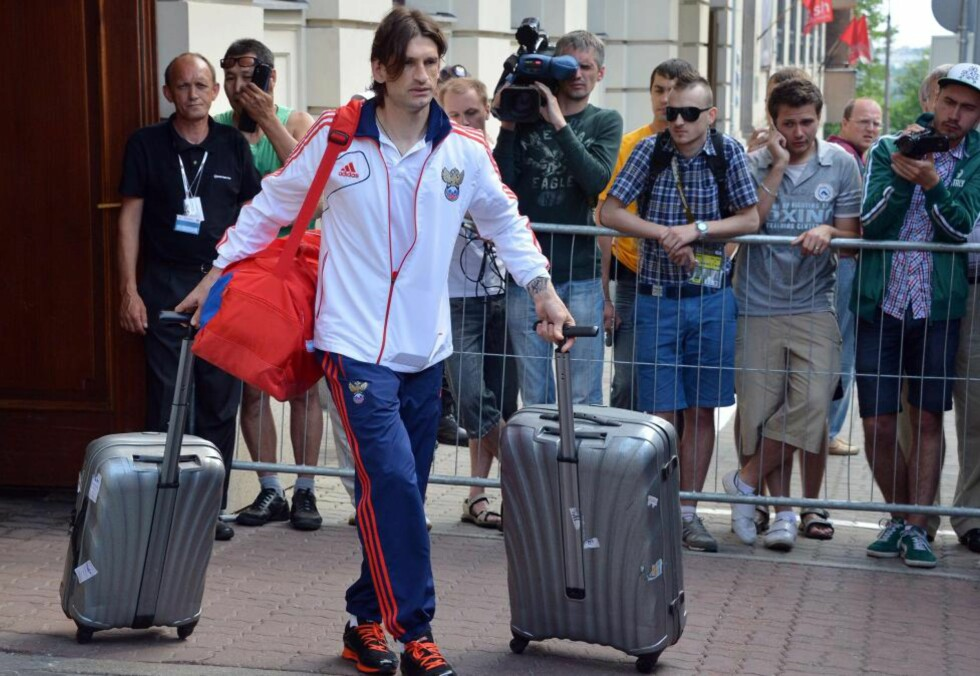 NÅ BÆRER DET HJEM: Russlands Roman Sharonov forlater Bristol hotel i polske Warszawa dagen etter tapet mot Hellas. Foto: AFP PHOTO / NATALIA KOLESNIKOVA / NTB scanpix