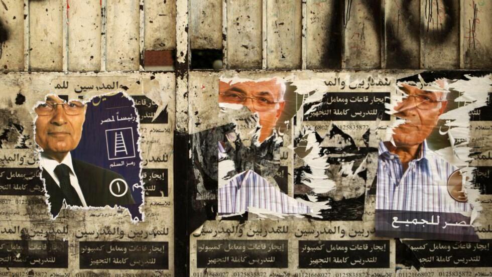 EN AV TO:  Tidligere general og statsminister under styrtede Hosni Mubarak - Ahmed Shafiq - på en sliten valgplakat utenfor et stemmelokale i Kairo. Helgens valg står mellom ZShaiq og Det muslimske brorskapets kandidat Mohammed Mursi. FOTO: PATRICK BAZ, AFP/NTB SCANPIX.