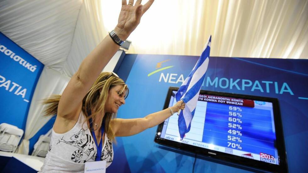 BLÅ VALGJUBEL:  En tilhenger av partiet Nytt Demokrati jubler etter at de første offisielle valgtallene er klare søndag kveld. Partiet får 128 av de 300 setene i parlamentet - inklusive de 50 bonusplassene som største parti - etter etter oppslutningen på 29,5 prosent. Anti-EU-partiet Syriza fikk 27,1 prosent, men bare 72 seter i parlamentet. FOTO: ANDREAS SOLARO, AFP/NTB SCANPIX.