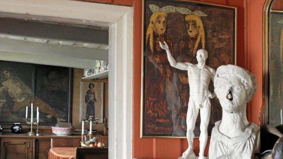 BOHEMLIV: Huset er fylt med malerier og skulpturer. Her har to skulpturer fått plass i hallen foran maleriet av Therese Nordtvedt. Den ene av stuene skimtes i bakgrunnen. Foto: Helge Eek