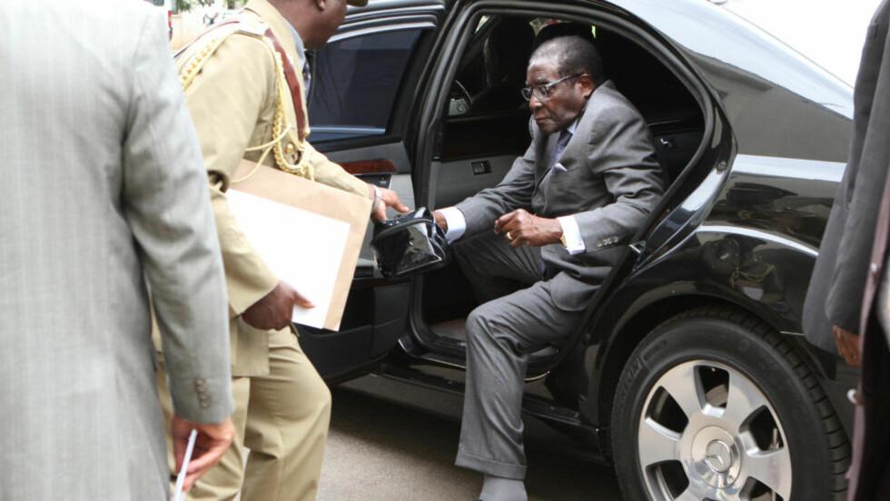 PÅKJØRSEL:Zimbabwes president Robert Mugabe kjører til sin hjemby med et stort følge når han er på besøk. Den som ikke kommer seg av veien når Mugabe kommer, utsetter seg for stor fare. Her ankommer han parlamentet i Harare. Foto: AP / Scanpix / Tsvangirayi Mukwazhi