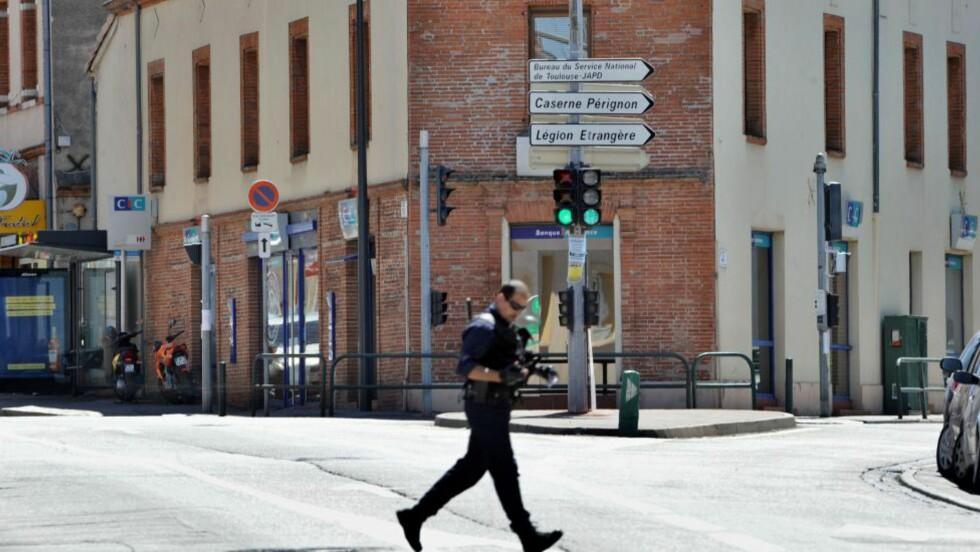 DRAMA:  En politimann løper over gata. I bakgrunnen skimtes banken der dramaet pågår. Foto: AFP PHOTO / ERIC CABANIS