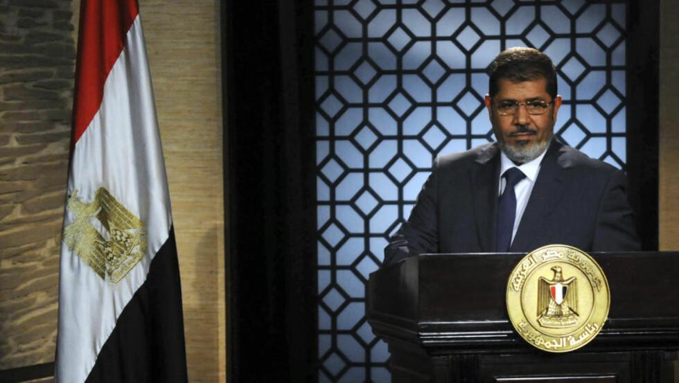 MED FLAGGET OG RIKSVÅPENET: Mohamed Mursi taler til folket etter at det ble klart at han vant presidentvalget i går. For litt over et år siden var Det muslimske brorskap, Mursis maktbase, forbudt.   REUTERS/Stringer