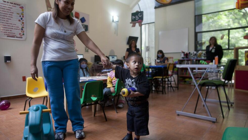 LYKKELIG: På dette bildet tatt i går, holder Jesus Rodriguez (2) moren Maria Fernandez trygt i hånda i et lekeområde på sykehuset La Raza Medical Center i Mexico City. Ved innleggelsen bar han på en 15-kilos godartet svulst. Foto: AP/Esteban Felix