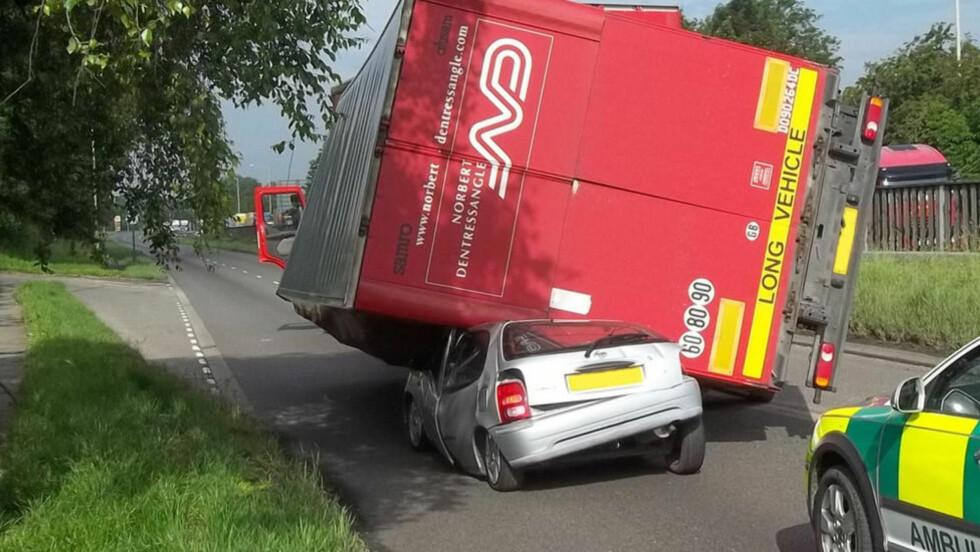 HADDE FLAKS: En 20 år gammel kvinne slapp så vidt unna med livet i behold da en lastebil plutselig veltet over bilen hennes. Foto: Caters News Agency / Bulls