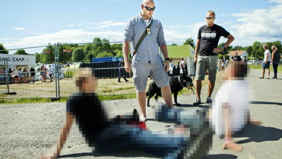 TATT: To unge menn blir tatt for besittelse av kokain og cannabis på vei inn på festivalen. Politibetjentene Jon Kristian Randgaard (skjorte) og Vidar Arnesen (svart t-skjorte), og politihunden Gordon, skal sørge for at Hovefestivalen ikke blir en rekrutteringsplass for narkotika. Alle foto: Anders Grønneberg