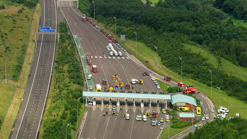 STENGT I BEGGE RETNINGER: Motorveien ble stengt i begge retninger etter meldinger om en person som oppførte seg mistenkelig i en buss på vei til London. Foto: AP Photo/SKY TV VIA APTN