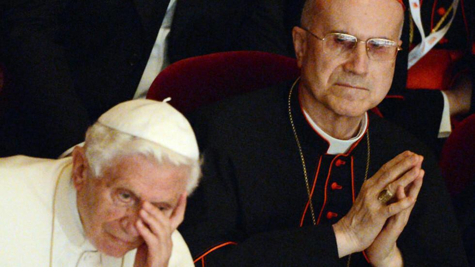 PROBLEMFYLT: Pave Benedict XVI har fått merke hvor problematisk det kan være med penger. Her står han sammen med kardinal Tarcisio Bertone, en mann som har vært sentral i den siste tidens Vatikan-skandaler. Foto: AFP/ DANIEL DAL ZENNARO