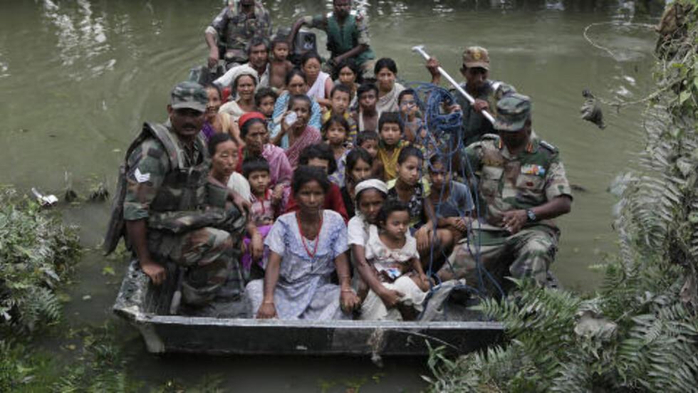 PÅ FLUKT: Seks millioner indere er blitt tvunget på flukt etter at kraftig regnvær har ført til store oversvømmelser i landet de siste ukene. Foto: AP / Anupam Nath / Scanpix