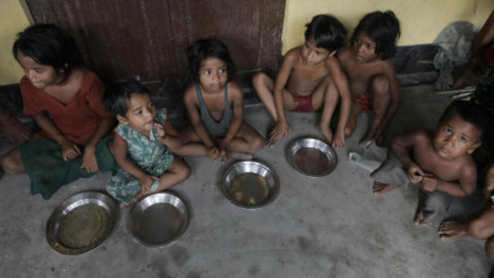 RAMMER BARNA: På en flykningleir  i Gauhati, øst i India sitter en gruppe små barn og venter på å få mat. Over en halv million mennesker er tvunget på flykt i det flod-rammede landet. Foto: AP / Anupam Nath / Scanpix