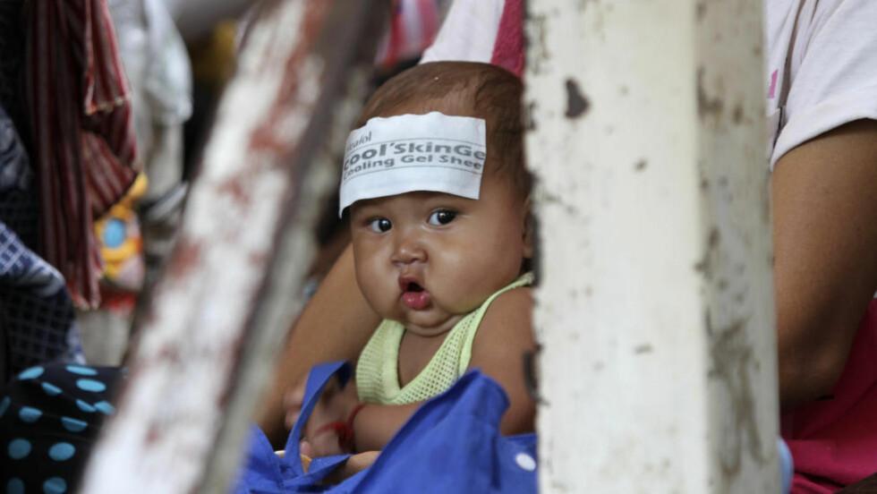 VENTER: 64 av 66 barn som har fått sykdommen er nå døde. Dette bildet er fra køen utenfor barnesykehuset den 4. juli i år. Foto: REUTERS/Samrang Pring/NTBScanpix