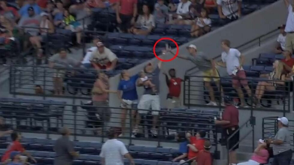 FARLIG?: Her fanger supporteren baseballen - med baby på armen. Foto: Skjermdump.