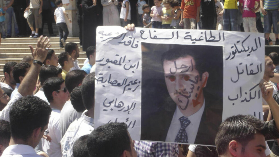 PREGET: Et portrett av president Bashar al-Assad i en anti-Assad demonstrasjon i opprørssenteret Al-Waar nær Homs.  REUTERS/Shaam News Network